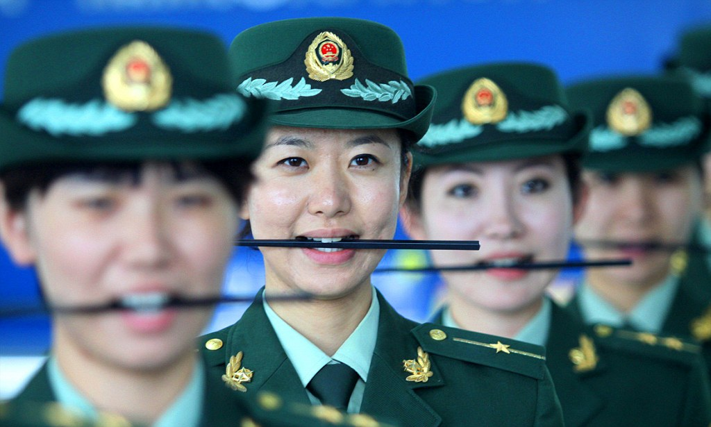 Mandatory Credit: Photo by HAP/Quirky China News / Rex Features (1941860b)  Female customs officials holding a stick between their teeth while smiling  Custom officials take part in a 'how to smile' course in Dalian, Liaoning Province, China - 28 Oct 2012  Female customs officials from Dalian in northeast China's Liaoning Province are seen taking part in a